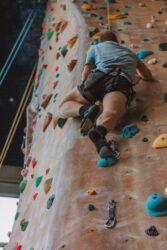 "<img src=""man climbing indoor wall.jpg"" alt=""sports protective gear""/>"